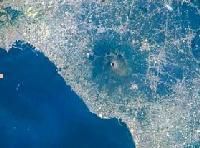 Esempio di urbanizzazione, (colore chiaro) intorno al cono vulcanico del Vesuvio (al centro). Napoli è in alto a sinistra (immagine ripresa dallo Shuttle nel 1996, fonte NASA